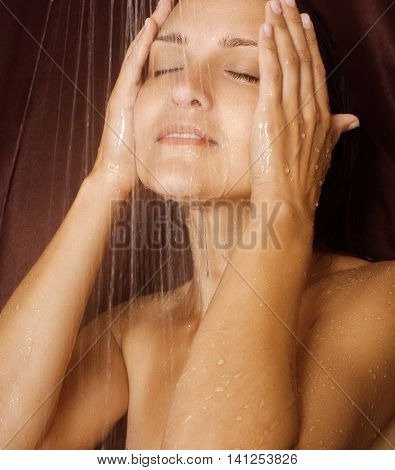 girl washes his face under a jet shower