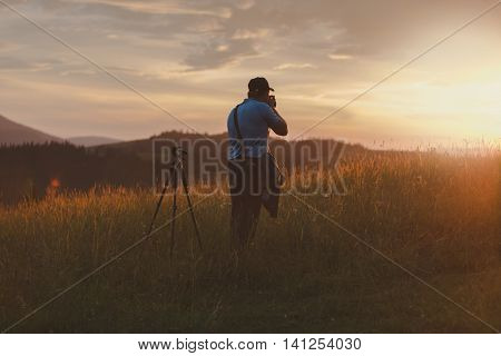 Photographer shoots landscape at sunset in the mountains