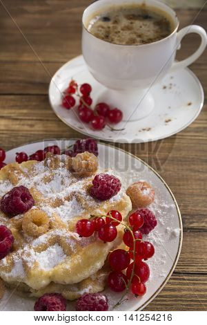 soft waffles with fresh berries, dusted with powdered sugar and a Cup of coffee