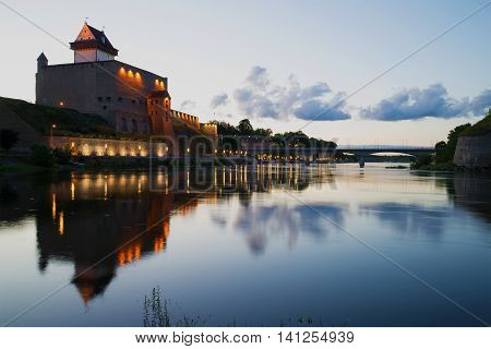 The old Herman's castle and the Narva river during the white nights. The border of Estonia and Russia