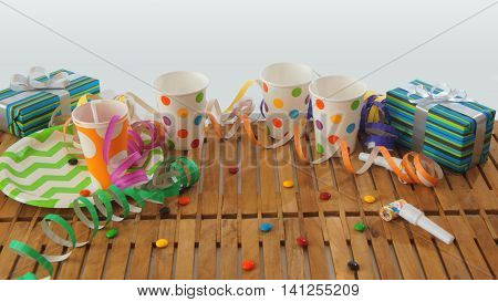 Rustic wooden table with colorful streamers, gifts, plastic cups, plastic plate, candies on white background. Party background