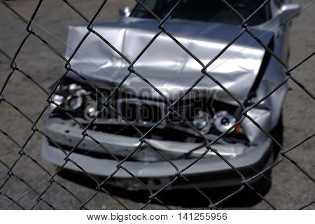 Car Wrecked with Smashed Hood and Grill Headlights behind Fence