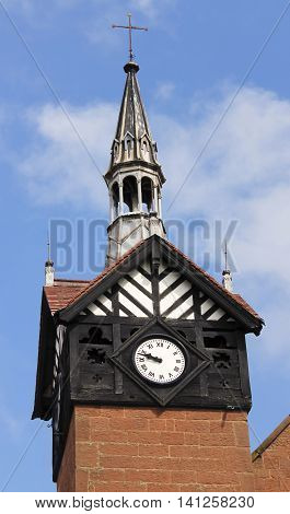 An Old Block and Timber Framed English Clock Tower Against a Blue Sky