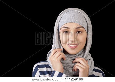 Portrait of a smiling young girl eastern appearance with his head covered in a Muslim-style on a black background Russia