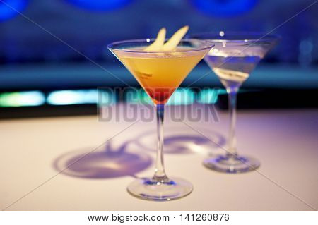 Two alcohol cocktails on the table in restaurant on blue background