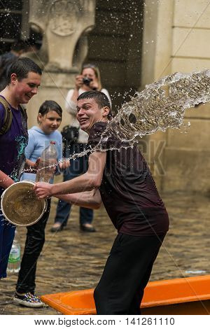 Lviv Ukraine - May 2 2016: Celebration pouring water on Monday after Easter by the town hall. Happy boys pouring water on each other.
