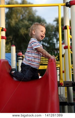 Child Sitting On Slide