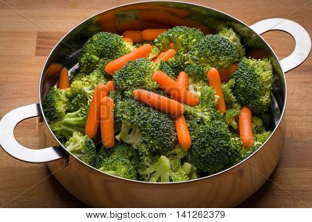 Fresh broccoli and carrots in stainless steel colander