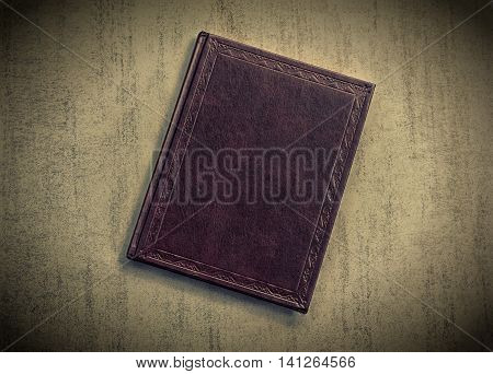 the book is dark purple on a grey grunge background top view. tinted photo with vignetting retro toned image