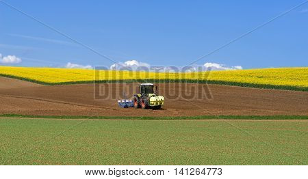 Tractor during sowing among fields in hilly landscape in spring