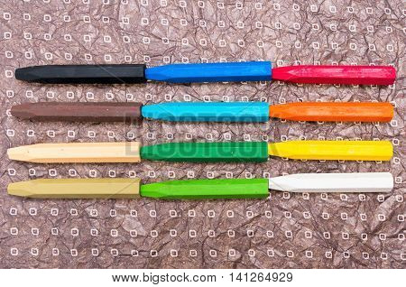 Oil Crayons with Bright Colors close up on a decorate paper sheet