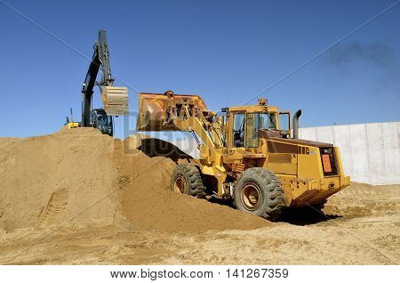 Heavy construction equipment is being used to move sand in a construction site.