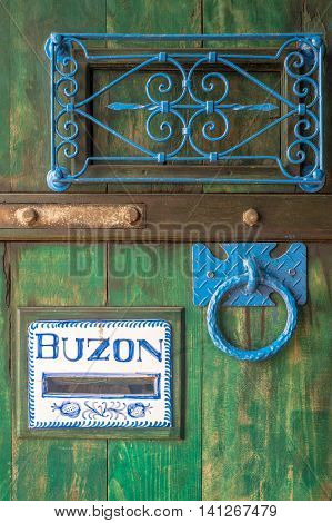 Wooden door with a slot mailbox and the word in Spanish means