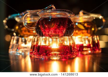 Three Glass Teapots With Candle Heaters;