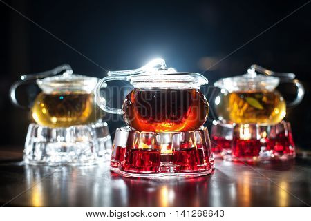 Three Backlighted Glass Teapots With Candle Heaters;