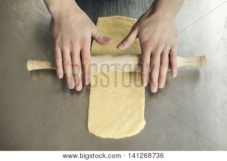 human hands unrolling dough; male work on kitchen and prepare food;