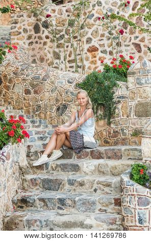 Young blond tourist woman sitting on ancient stone stairs in the Old city, Alanya, Meditarranean region, Turkey.