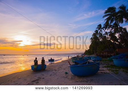 The Round Silhouettes Of Fishermen And Boats At Sunset In Vietnam.