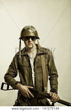Brave young soldier with rifle posing over white background