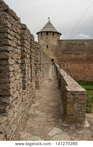 Russian medieval castle in Ivangorod. Located on the border with Estonia, not far from St. Petersburg. The photo shows a passage through the wall of the fortress and watchtower. Photographed on a cloudy day.