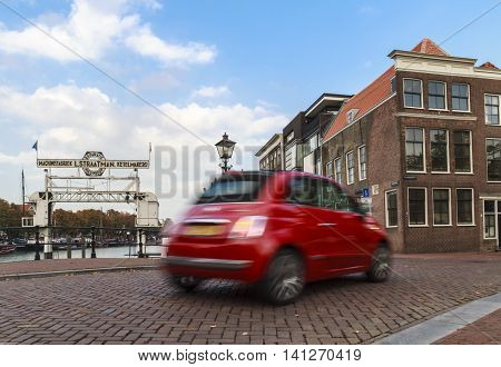 DORDRECHT NETHERLANDS - OCTOBER 9 2015: Shiny red Fiat 500 with motion blur driving in the old center of Dordrecht.