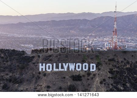 Los Angeles, California, USA - July 21, 2016:  Late afternoon aerial of the Hollywood Sign in Griffith Park with the San Fernando Valley and San Gabriel Mountains in background.