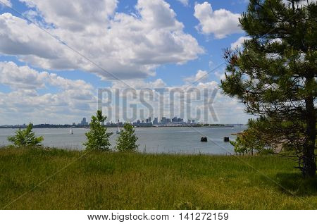 Beautiful puffy white clouds hanging over Boston harbor with views of the city in the distance.