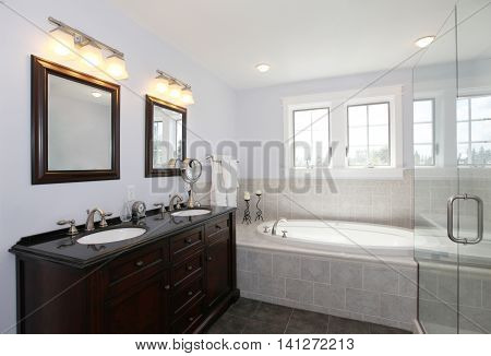 Bathroom With Tub And Wood Cabinet With Two Sinks