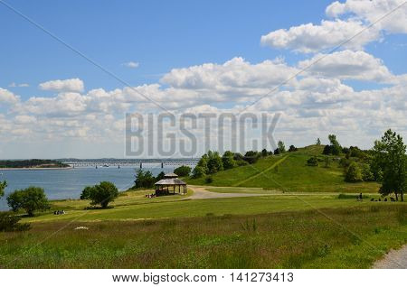 Hiking trails on Spectacle Island on a beautiful day with fluffy white clouds in the sky.