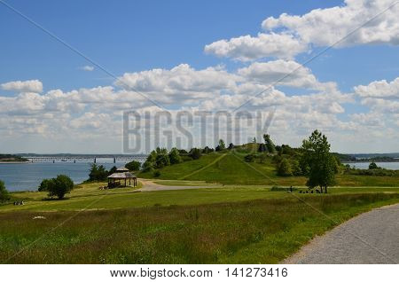 Lush Spectacle Island with fluffy clouds and green grass.