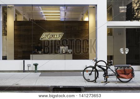 New York NY USA -- Aug 3 2016 A storefront office with a glass exterior wall and a bycycle parked outside. Editorial Use Only