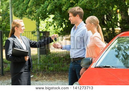 Young Saleswoman Giving Car Key To Happy Couple