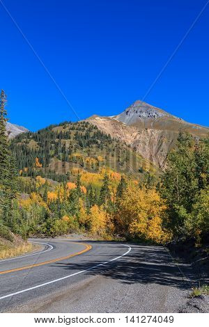 a highway winds through the scenic landscape of southwest colorado in fall