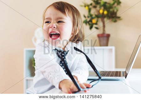 Happy Toddler Girl Laughing While Using A Laptop