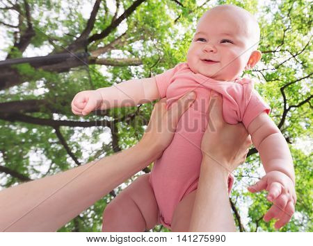 Happy Infant Baby Girl Being Held Up In The Air