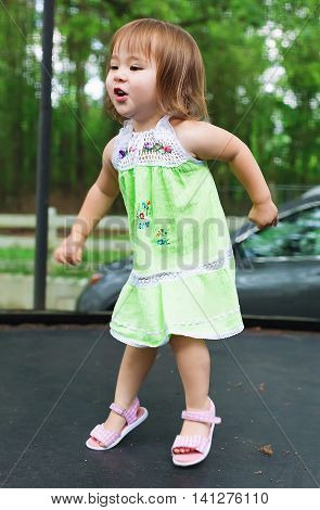 Happy Toddler Girl Jumping On A Trampoline