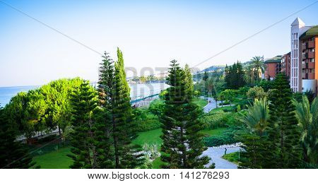 Scenic panoramic view of park and beach at Avsalar Alania Turkey Mediterranean sea blue sky. Tropical landscaping with planting conifers and trees lawn foliage grass and fences. Copy space.