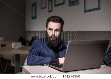 Bearded Man In Suit And With Laptop Sitting In Cafe And Browsing Internet;