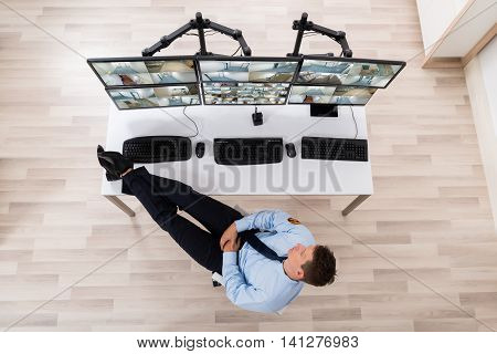 High Angle View Of Security Guard Sleeping In Front Of Multiple Computers Showing CCTV Footage