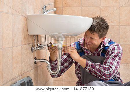 Smiling Male Plumber Repairing Sink In Bathroom
