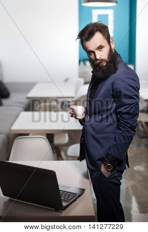Bearded Man In Suit With Laptop And Cup Of Coffee In Cafe;