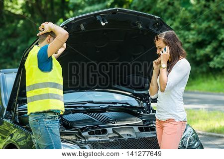 Man Looking At Woman Talking On Mobile Phone With Broken Down Car On Street