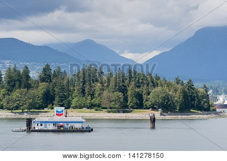 Vancouver Canada - July 23 2016: Chevron artificial island fueling station in Vancouver harbor. For small boats and water planes. Background is Stanley Park and the mountains farther away. Heavy clouds in the sky.