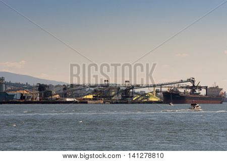 Vancouver Canada - July 24 2016: Bulk Ship loads up in Vancouver harbor. Mounts of yellow sulfur and brown woodchips partly hidden by transport belts bridges and other loading equipment. Clear skies.