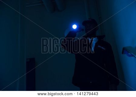 Male Security Guard In Black Uniform Holding Flashlight