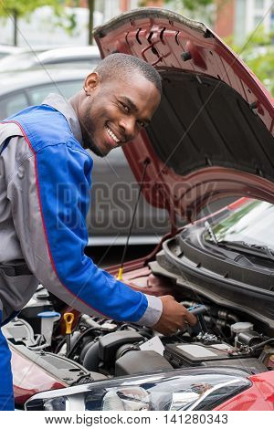 Young Happy Male Mechanic Testing Car Battery With Multimeter