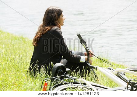 Young Businesswoman Sitting By Lakeside Near Bicycle