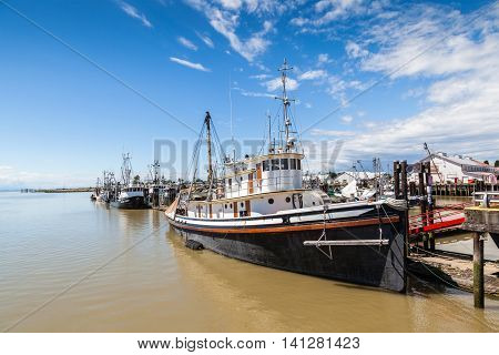 RICHMOND CANADA - JULY 10: Colorful boats and trawlers dock at the seaside village of Steveston Fisherman's Wharf in Richmond near Vancouver July 10 2016. The place was a 19th-century frontier seaport more than 100 years ago.