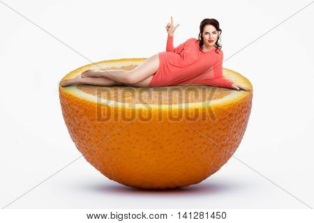 Small Female Lying On Half Of Giant Orange; Woman On Diet,