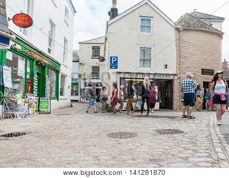 Mevigissey, England - July 25, 2013: People milling about  on cobbled towns street and lane modern living in typical historic English fishing and port village Mevigissey in Cornwall England